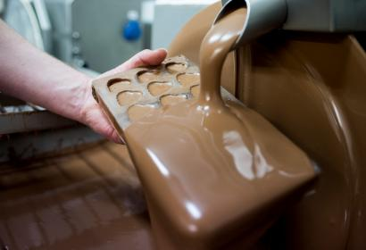 Chocolat pouring over mould at chocolate factory Cyril in Wallonie